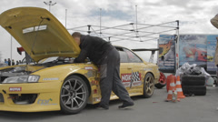 Racer repairs yellow race car Stock Footage