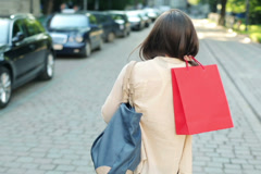 Woman with shopping bags walking in the city, steadicam shot NTSC Stock Footage
