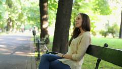 Happy attractive woman relaxing on bench in city park HD - stock footage