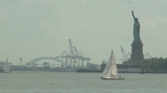 Statue of Liberty, yacht sails thro fore ground Stock Footage