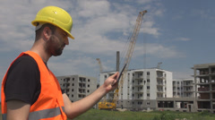 Stress at construction site engineer working on tablet interrupted by phone call - stock footage