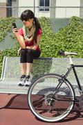 sportive woman with fixie bike looking smartphone - stock photo
