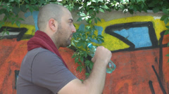 Terrible heat outside young man drinking water cooling using towel graffiti wall Stock Footage