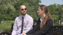 Young man with sunglasses unleashing tie while relaxing with a teammate outside Stock Footage