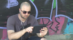 City young boy gaming on tablet being happy to win leaning on graffiti wall play Stock Footage