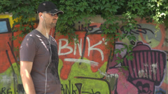 Street stylish boy with cap sunglasses headphone feeling the music graffiti art Stock Footage