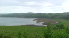 Loch or fjord head amound the green hills, pan Stock Footage