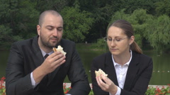 Business job for man woman couple eating sandwich outdoor checking time on clock Stock Footage