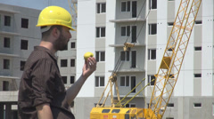 Windy summer day outdoors construction worker eating an golden apple wipe sweat Stock Footage