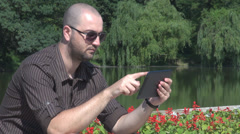 Beautiful young man with sunglasses working playing on tablet relax moments out Stock Footage