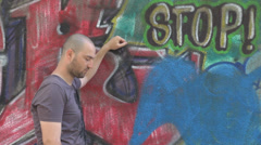 Angry upset pissed town boy hitting with fist a wall graffiti painted frowning Stock Footage