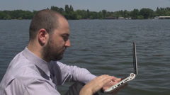 Businessman is online working wireless on laptop near a lake relax in park area  Stock Footage