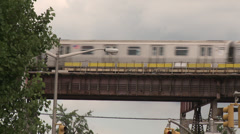New Silver York Subway train on raised track with blue sky behind Stock Footage