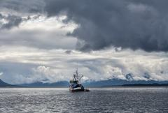Stormy skies with fishing boat Stock Photos