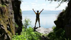 Backpacker comes to coast of lake Stock Footage