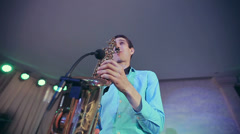 Saxophone player performs on stage with professional light. Close up wide angle Stock Footage