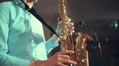 Saxophone player performs on stage with professional light. Profile shot. - stock footage