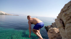 Slow-Mo: Young Muscular Man Jumps Headfirst Into Crystal Clear Blue Water Stock Footage