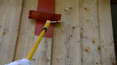 Closeup of roller brush paint wooden plank outdoor house wall - stock footage