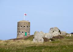 loophole towers in guernsey that guard the coastline. - stock photo