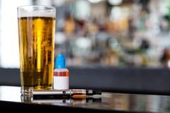 beer, e-liquid and vaporizer on the bar - stock photo