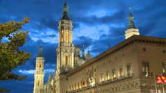 Catholic Basilica and City Hall lit with dark blue cloudy sky Stock Footage