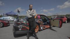 Racer stand near sports car Stock Footage