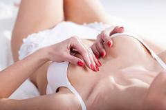 sensual woman covers her breasts - stock photo