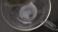 Teabag falling into glass cup Stock Footage