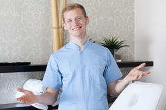 male dermatologist showing welcome gesture - stock photo