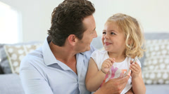 man with cheerful little girl playing with smartphone - stock footage
