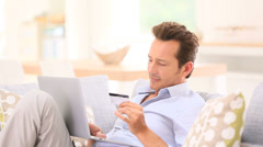 Handsome man relaxing in sofa and shopping on internet Stock Footage