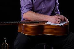 Guitarist writing a song Stock Photos