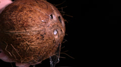 Water leaking out of coconut on black background - stock footage