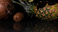 Stock Video Footage of Kiwi slices falling in front of pineapple and coconut