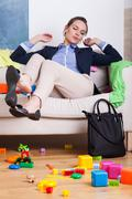 businesswoman sitting on couch at messy room - stock photo
