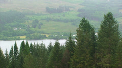 Loch and farms down on the valley behind spruce tree forest, Stock Footage