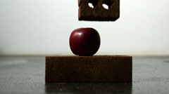 Apple being squashed between two bricks Stock Footage