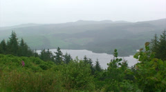 Loch and hazy mountains behind the spruce trees Stock Footage