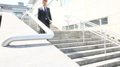 Businessman walking down stairs in town Stock Footage