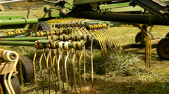 Haymaking  machine in run. Big green tractor with hay maker working on meadow Stock Footage