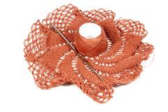Salmon colored crocheted doily with crochet hook Stock Photos
