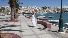 Woman walking along the waterfront os sea Stock Footage