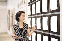 woman looking at notice board in hall - stock photo
