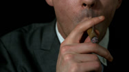Stock Video Footage of Businessman smoking his cigar on black background
