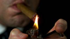 Businessman lighting his cigar on black background - stock footage