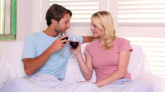 Couple sitting on sofa under blanket having red wine Stock Footage