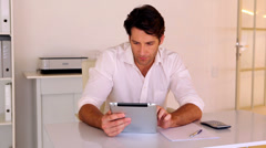 Businessman using tablet pc at his desk Stock Footage