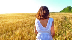 Happy, young woman with a toothy smile running across the wheat field - stock footage