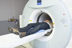 Low section of male patient lying in MRI scanner Stock Photos